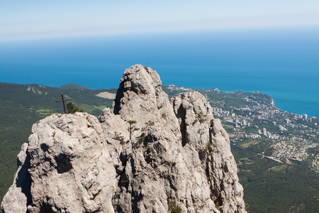 High rocks Ai-Petri of Crimean mountains with cross against a green forest, Black sea coast and blue sky. Russia.