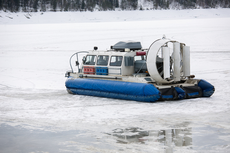 Hovercraft transporter on the ice of river in winter day