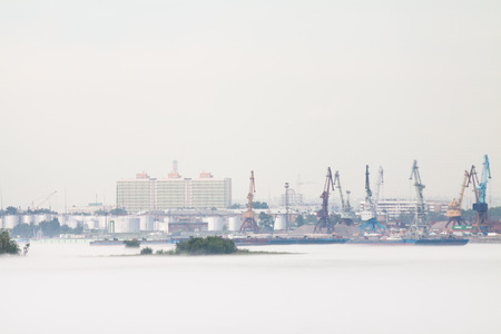 Cranes and industrial barges in the port, against a background of cloudy weather with fog in the summer. Russia, Krasnoyarsk.