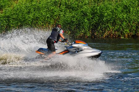 Man on jet ski turns left with much splashes. Nice