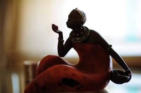 STATUETTE. Dark-skinned girl sitting. Beautiful girl