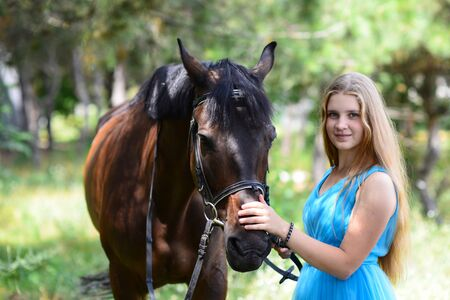 outdoor portrait of young beautiful woman with horse. Against the background of a tree. Reklamní fotografie