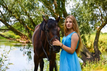 outdoor portrait of young beautiful woman with horse. Against the background of a tree.