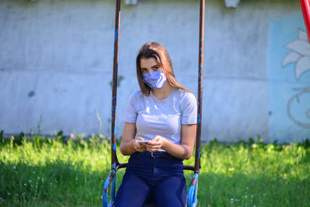 Smiling young model relaxing in a sunny garden sitting on swing. 版權商用圖片