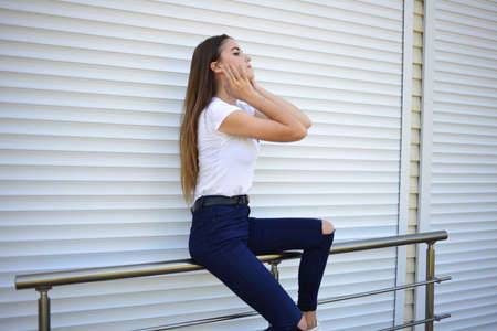 Beautiful young woman wearing jeans, white t-shirt, standing on the street. photo near iron fence.