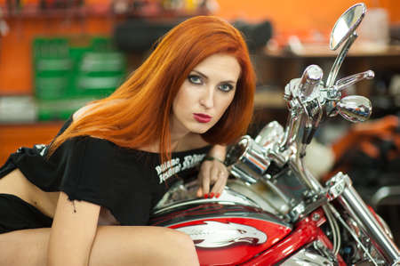 beautiful red-haired girl and motorcycle in the garage.