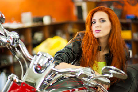 Portrait of charming young woman with red hair near a motorcycle