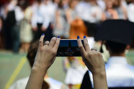 Woman using smartphone taking picture at graduation party. Foto de archivo