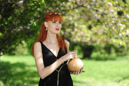 Young beautiful woman with red hair in a black long dress in a spring garden on a background of blooming sakura.