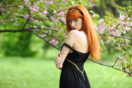 Young beautiful woman with red hair in a black long dress in a spring garden on a background of blooming sakura. Banco de Imagens - 157508254