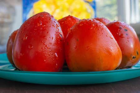 ripe, juicy orange persimmon on a bluish green plate. Foto de archivo