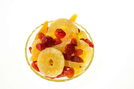 Yellow candied melon slices, pineapple rings and dogwood in a glass vase on a white background, top view in a glass vase on a white background, top view. Banco de Imagens