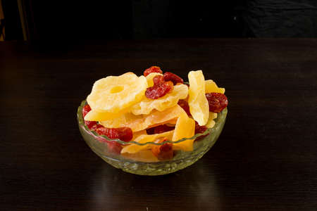 Yellow candied melon slices, pineapple rings and dogwood in a glass vase on a black background. Banco de Imagens