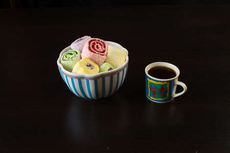 Turkish Delight in a porcelain vase and a cup of coffee on a black background.