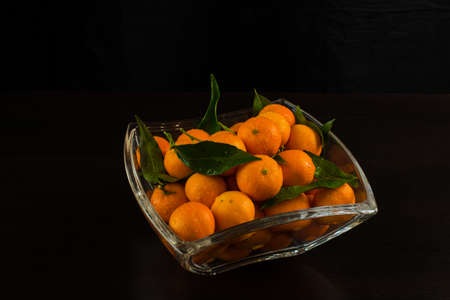 Glass vase with tangerines. Decor for the New Year and Christmas. stands in a glass vase on a black background, top view
