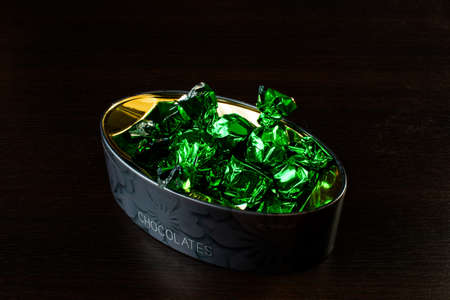 box with candy in green foil wrappers on a black background Banco de Imagens