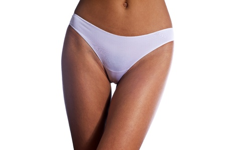 young sexy slim tanned girl in white panties on white background photo