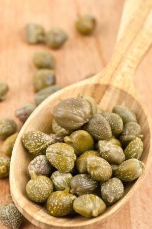alcaparras: deliciosas alcaparras en cuchara de madera