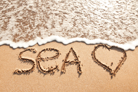 word sea on beach sand photo