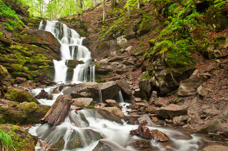 cascading waterfall in the mountain photo