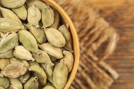 dry food: heap of dry cardamom on burlap napkin