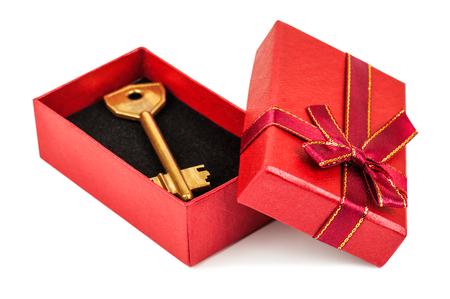 Clé d'or dans une boîte cadeau rouge sur fond blanc Banque d'images - 49582981