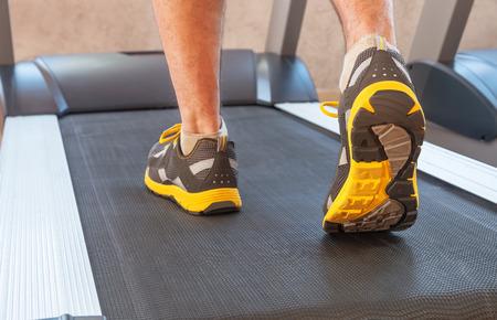 L'homme de sport dans une salle de sport sur tapis roulant dans les chaussures de sport Banque d'images - 51038422