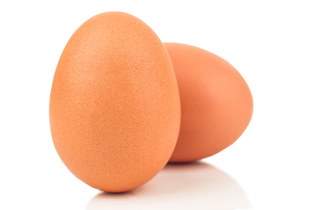 emerge: two raw chicken eggs on white background