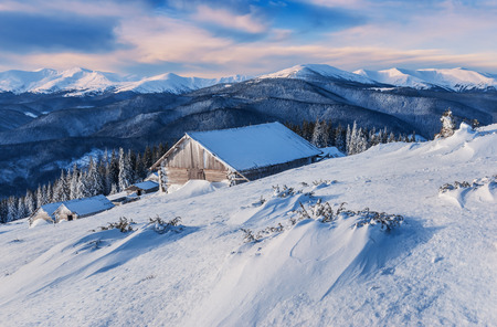 snowdrifts and abandoned hunting chalets (cabin) in winter mountains Stock Photo