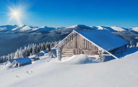 wintery day: cabin (hut) under blue sky in winter mountains Stock Photo