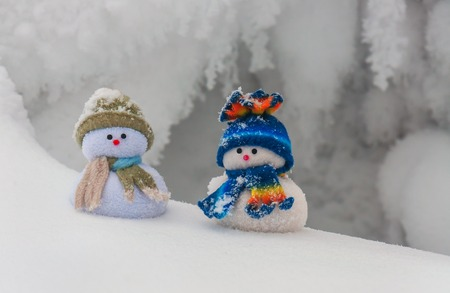 snow drift: two funny snowmans on the snow drift Stock Photo