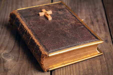 bible reading: old closed holly Bible with wooden christian cross