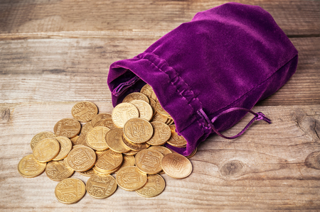 ukranian: ukranian coins and purple pouch on wooden background