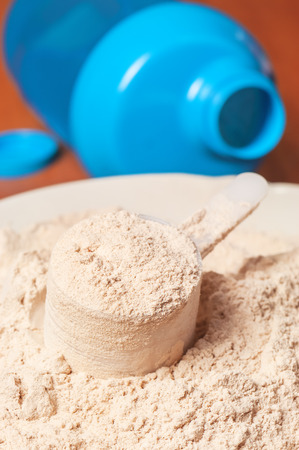 surrogate: protein powder with plastic spoon and blue shaker