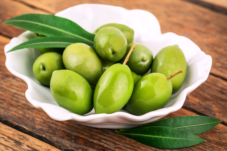 ripe green olives with leaves in bowl Stock Photo