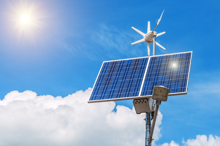 breaking new ground: working solar panel with windmill under the sun Stock Photo