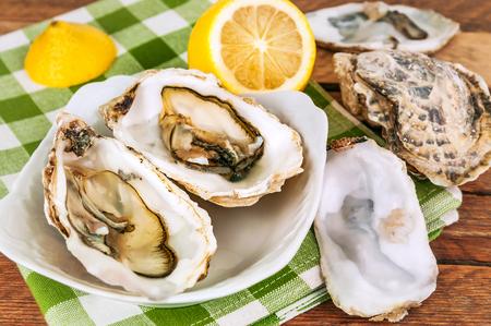 fresh opened oysters with lemon juice Stock Photo