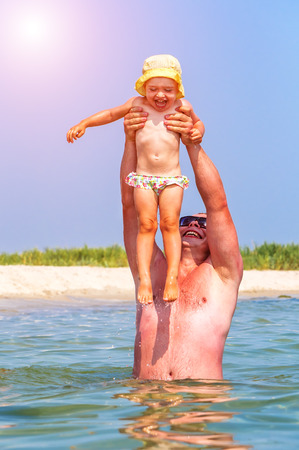 happy little daugther with father in the water (sea)