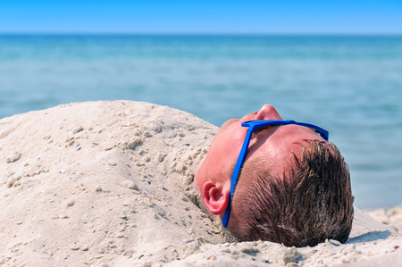 man with blue sun glasses buried in the sand on the beach