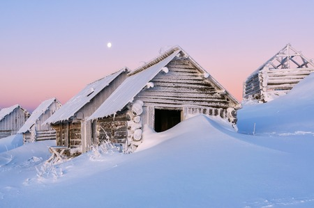 snow drift: Abandoned cabins in snow drift. Winter theme. High mountains. Beautiful sunrise