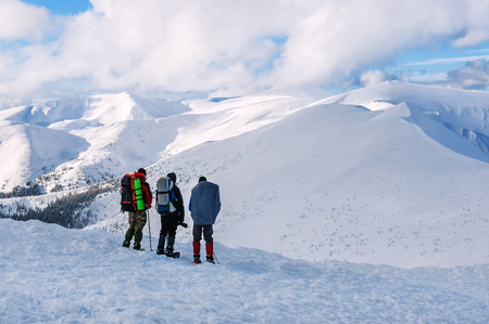 three tourists with backpacks stand in high winter mountains