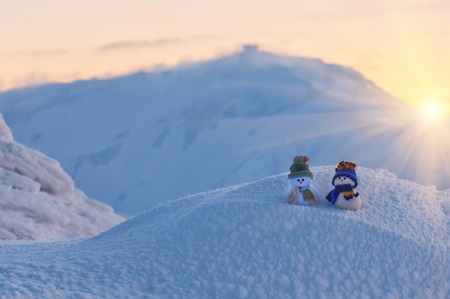 two snowmen in winter high mountain