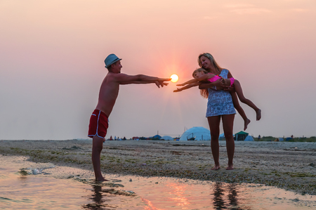 young happy family on the beach at sunset
