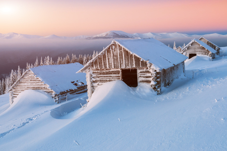 abandoned cabins in high winter mountains. Beautiful sunrise. Snow drifts