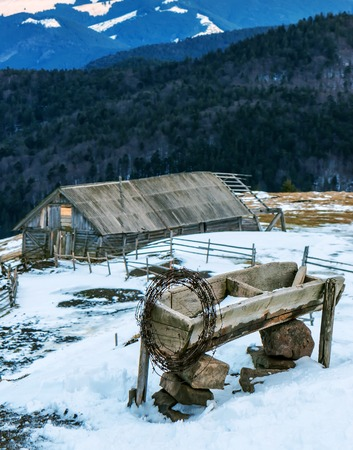 rusty barbed wire and cabin in winter mountains