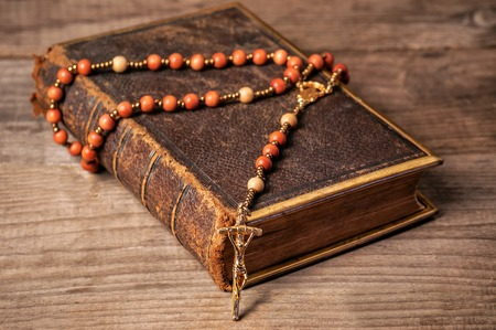 Holly Bible in leather cover with rosary Stock Photo
