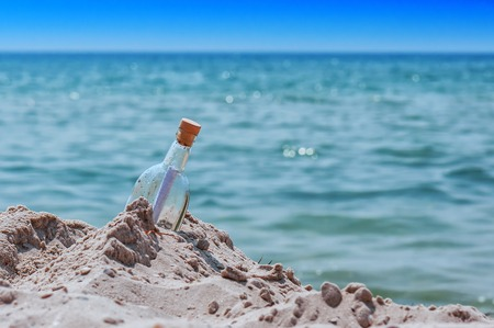 bottle with a note in the sand on the beach, near the sea