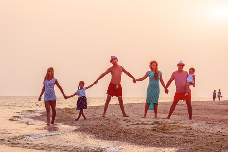 two friendly families holding hands on the beach in sunset time Stock Photo