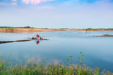 landscape with fisherman and lake in sunset time Stock Photo