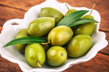 heap of green ripe olives with leaves Stock Photo